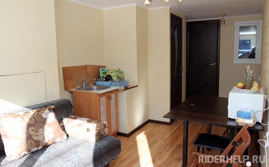 В кухне удобный диван для посиделок, обеденный стол, раковина